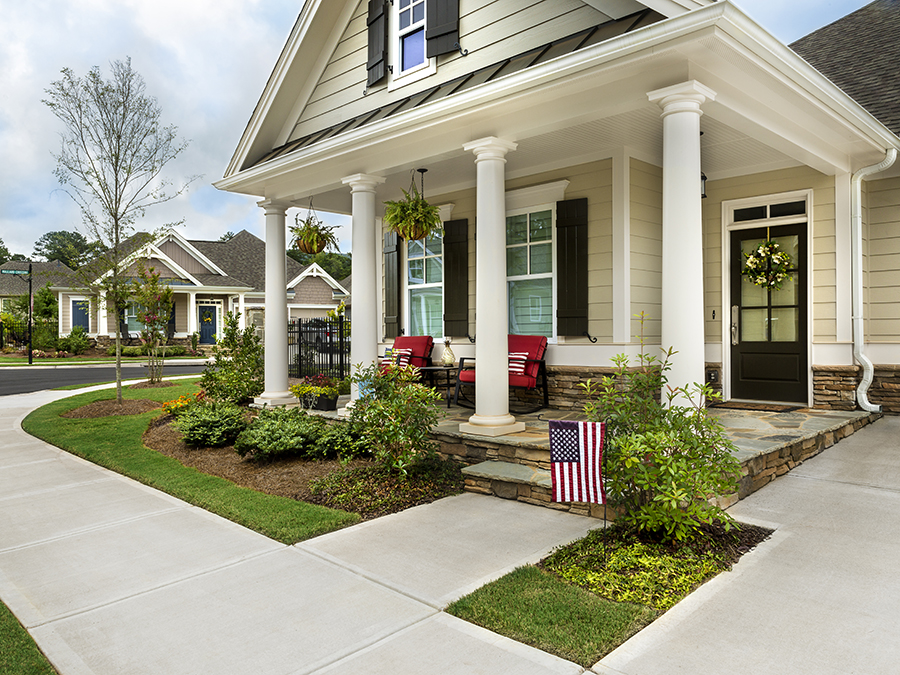 Beautiful home with streetscape in backround and American flag in the yard