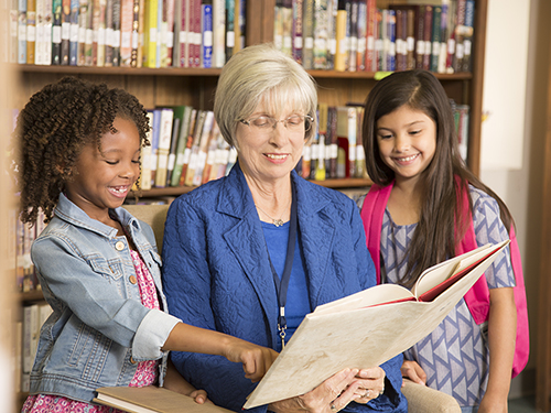 Senior woman mentoring young kids in a reading program>