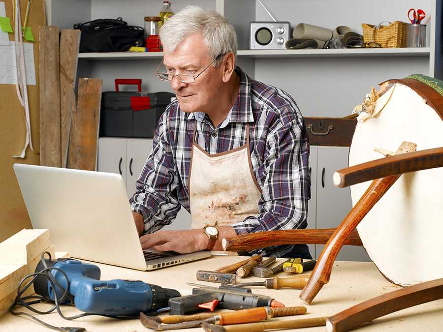 Woodworker fixing a broken chair in his garage