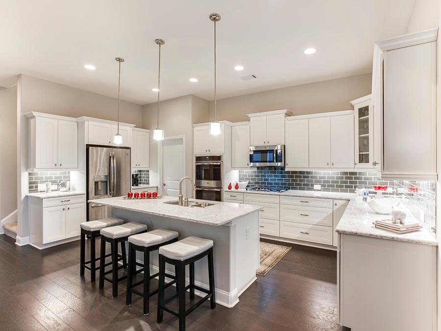 Wide open kitchen concept with island, white cabinets, marble countertops and stainless steel appliances in the Harrison new house plan available at the McConnell Green 55+ active adult community in Powder Springs, GA.
