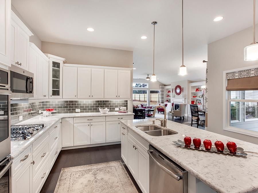 Large open kitchen with white cabinets, marble countertops and stainless steel appliances in the Harrison new home plan available at the McConnell Green active 55+ community in Powder Springs, GA.