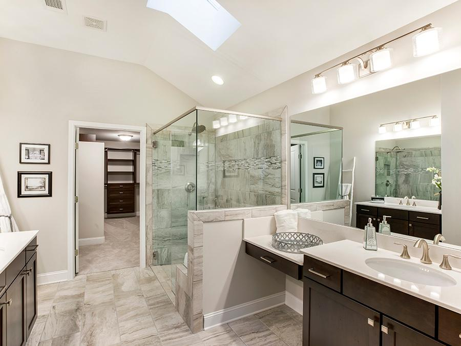 Magnificent tiled master bathroom with two vanities, marble countertops and stainless steel faucets in the Harrison new house floor plan available at the McConnell Green 55 and older community in Powder Springs, GA.